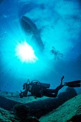 Wall Mural - boat ship from underwater blue ocean with sun rays and scuba diver