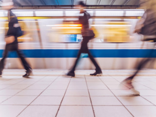Subway train leaving station. People coming to or leaving the platform. Motion blur. City life.Toned image.