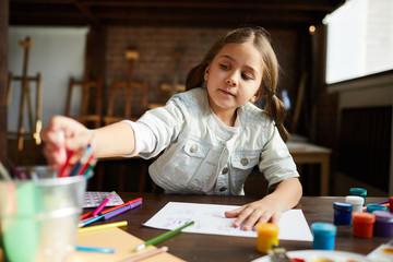 Portrait of cute little girl painting pictures in art class or at home, copy space