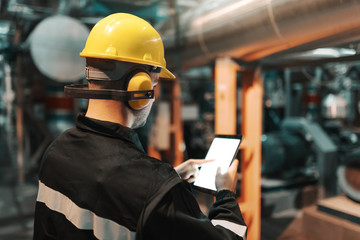 Caucasian worker in heavy industry plant with helmet and in uniform using tablet for work.