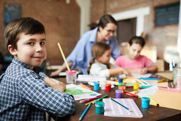 Portrait of smart little boy looking at camera while painting pictures in art class with group of children, copy space