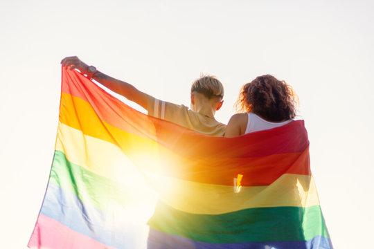 A beautiful lesbian young couple gently lovingly embraces and holds a rainbow flag, equal rights for lgbt community,