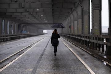 Girl walking on bridge on a rainy day