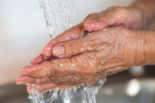 Senior woman washing her hands, Flowing and  Splashing water, Close up & Macro shot, Selective focus, Healthcare concept