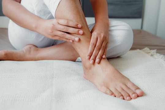 Close-Up of Woman Hands is Massaging Her Ankle on Bedroom, Young Adult having Legs Ache After Home Work. Healthcare and Medicine Concept.