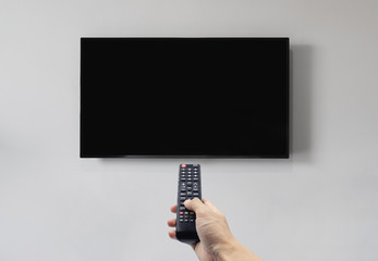 Television on white wall with hand using remote control, blank black screen