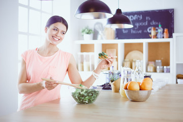 Smiling young woman mixing fresh salad in the kitchen.