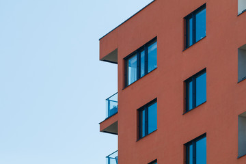 Photo of a new modern residential building with blue sky.