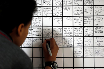 A student writes a note for his mother on a poster as part of an attempt to break the Guinness World record for the world's largest sign with wishes for Mother's Day, in Amman