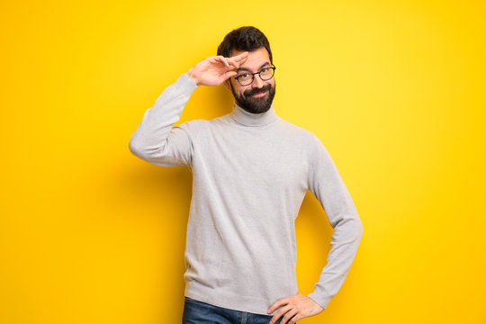 Man with beard and turtleneck saluting with hand
