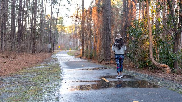 woman with hat walking down empty bath in woods