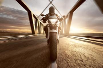 Fototapete - Motorradfahrer auf Brücke im Sonnenuntergang