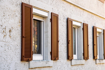 House facade with two windows with old wooden shutters with slats