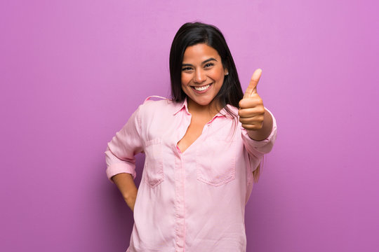 Young Colombian girl over purple wall with thumbs up because something good has happened