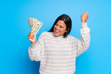 Young Colombian girl with sweater taking a lot of money