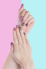 Aluminium Prints Manicure Beautiful young woman's hands isolated on pastel pink and blue background. Stylish trendy female manicure with gray, pink and brown nail polish.