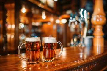 Two beer mugs on wooden bar counter, nobody