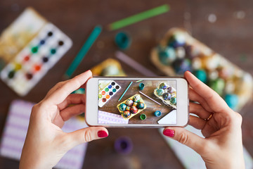 Top view closeup of unrecognizable woman taking photo of handmade Easter eggs with mobile phone, copy space