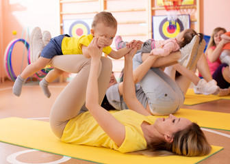 Mothers do fitness exercises together with their kids in daycare gym