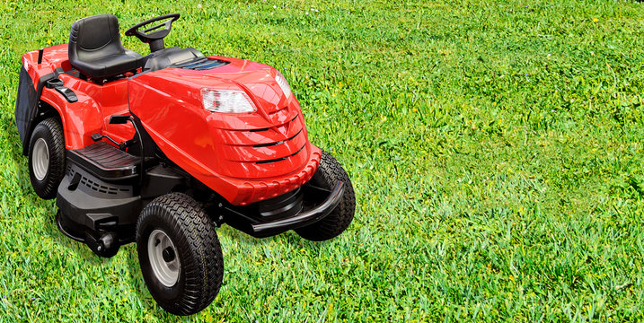 Gardening equipment advertisement template - red tractor mower on a green grass in the garden with copy space.