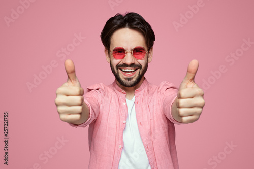 99bac207 Portrait of trendy young man in pink stylish shirt and sunglasses showing  thumb up over pink background