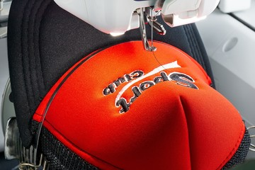 Close up picture of red cap on the hoop of embroidery machine