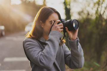 Travel photo of attractive girl making pictures on camera while road trip