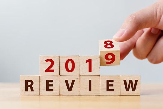 2019 review concept. Hand flip wood cube change year 2018 to 2019 and the word REVIEW on wooden block on wood table
