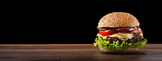 Fototapeta Homemade hamburger close-up with beef, tomato, lettuce, cheese and onion on wooden table. Fastfood on dark background obraz