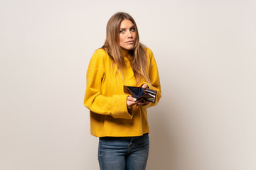 Woman with yellow sweater over isolated wall holding a wallet