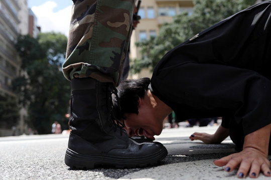 """Venezuelan artist Deborah Castillo licks the boots of a man dressed as a member of the military during her performance """"Lamebrasil, Lamezuela - questioning power in Latin America,"""" in Sao Paulo"""