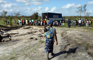 A women with a baby on her back arrives to receive food parcel from an aid organisation after Cyclone Idai, near Dondo