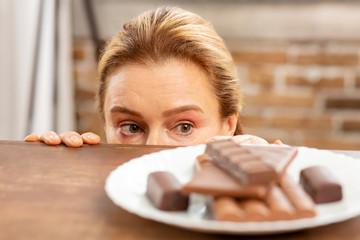 Green-eyed mature woman hiding and looking at dark chocolate