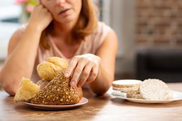 Woman allergic to gluten taking little bun with seeds