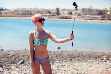 Travel, leisure, summer, technology and people concept - young woman with pink hair taking selfie on beach background