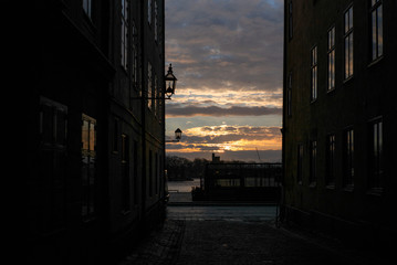 Sunrise sun filtering through on the old cobbled narrow street with colorful houses in Stockholm in...