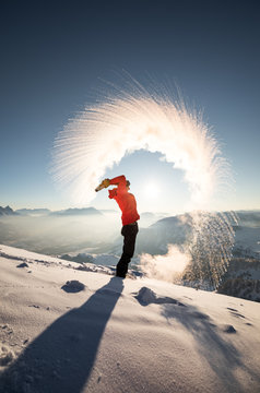 A hiker in the austrian alps throws a bottle full of boiling water in the air. Rapid freezing happens when the temperature difference is big enough. Water turns into snow particles.