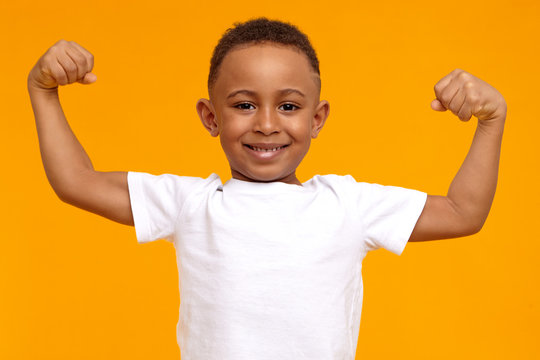 Handsome confident Afro American eight year old child in casual t-shirt smiling happily and raising clenched fists, tensing muscles, feeling strong and full of energy after ate healthy protein lunch