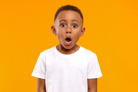 Surprise, excitement and fascination concept. Funny bug eyed African little boy opening his mouth widely, shocked with astonishing unexpected news, having amazed look, showing full disbelief