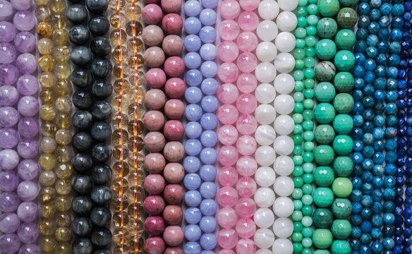 Beads from various types of natural stones are strung on a thread.