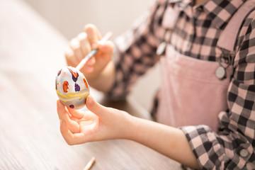 Girl painting Easter egg
