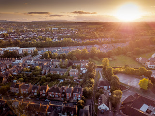 Sunset over traditional British houses with countryside in the background. A picturesque scene, created by the long shadows and warm glow