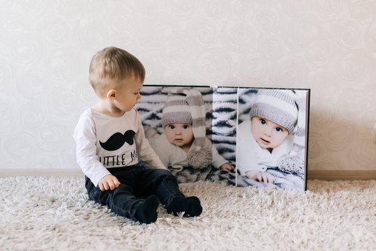 Cute baby sitting on the background of a large stylish photo book with your photos