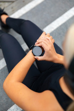 Woman runner setting up the fitness smart watch for running