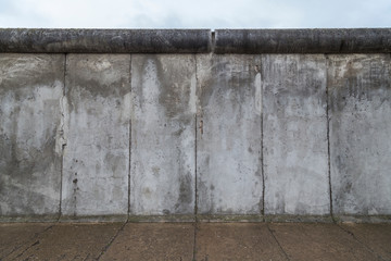 Front view of a section of the original Berlin Wall at the Berlin Wall Memorial (Berliner Mauer) in Berlin, Germany, on a cloudy day.
