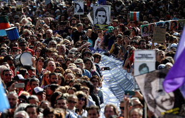 Demonstrators hold banners with images of people who disappeared, during the march towards Plaza de Mayo square to commemorate the 43rd anniversary of the 1976 military coup, in Buenos Aires