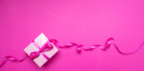 Wall Mural - Gift box with ribbon on pink background. Birthday present concept.