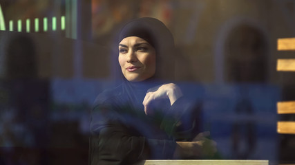 Attractive Muslim lady in hijab sitting in cafe, looking in window, dreaming
