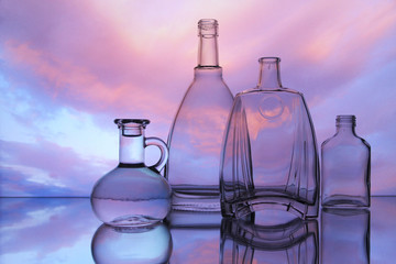 Empty glass bottles. Transparent forms for cold drinks, randomly presented and on a sky background. Presentation of glass forms in the industrial production of glass.