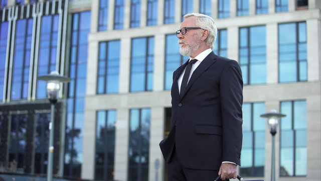 Grey-haired company director standing outdoors, confident businessman waiting